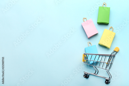 Cuadros en Lienzo Small paper shopping bags with shopping cart on blue background