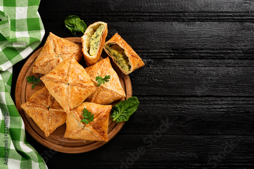 Puff pastry squares filled with potato, cheese and spinach on black wooden table Fototapet