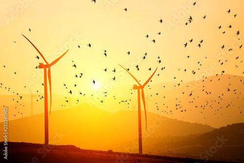 Wind power generators on the background of silhouettes of mountain peaks and a flock of birds. Simplicity and minimal lines. Beautiful landscape of the power of nature.