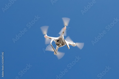 Canvas Print Flying Dron with a camera on a blue sky background.