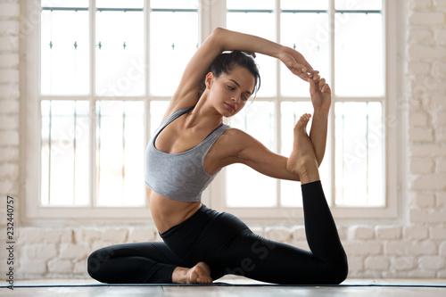 Carta da parati Young sporty attractive woman practicing yoga, doing Mermaid exercise, Eka Pada