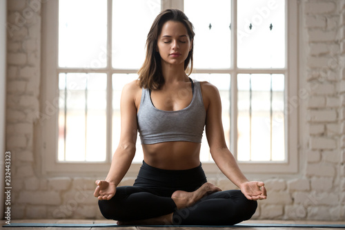 Young sporty attractive woman practicing yoga, doing Ardha Padmasana exercise, meditating in Half Lotus pose with mudra gesture, working out, wearing sportswear, indoor full length, white yoga studio
