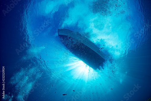 Fotografering boat ship from underwater blue ocean with sun rays