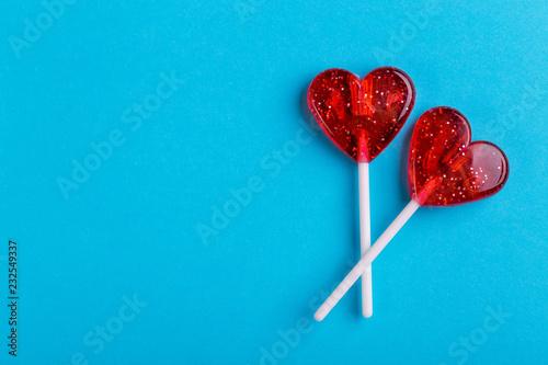 Two red sweet tasty lollipops in shape of heart