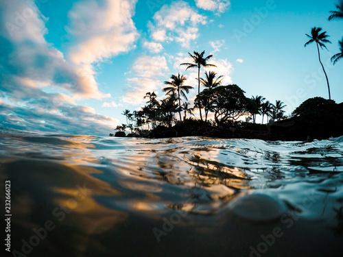 Carta da parati Clear Aqua Blue Water with Reflection of Colorful Morning Sunrise Sky off Glassy