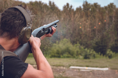 Fotografia man in soundproof headphones shoots a hard disk at flying plates