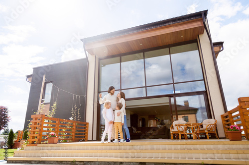 Young people with little children standing outdoors on summer terrace. Parents and kids embracing, husband holding keys from their new big and modern house. Happy family and real estate owners concept