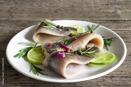 fillet of herring with pepper, rosemary, onion and lime in a plate on rustic wooden background. close up