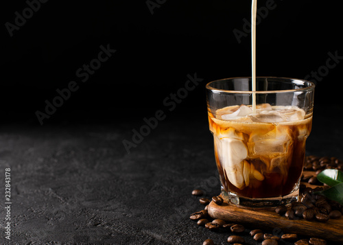 Fotografia glass cold brew coffee with ice and milk on black or dark background