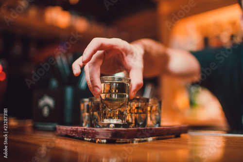 Fotografia Bartender is pouring tequila into glass against the background of the bar