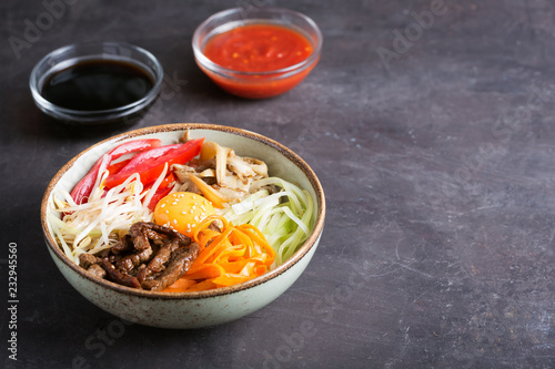 Traditional Asian Bibimbap dish with rice and vegetables on dark background with copy space