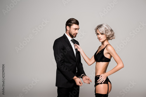 Fototapeta Beautiful woman pulling by cravat handsome man in costum and handcuffs isolated