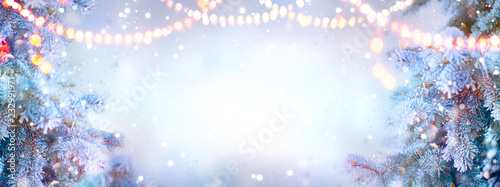 Christmas background. Xmas tree with snow decorated with garland lights, holiday festive backdround. Widescreen frame backdrop. New year Winter art design, Christmas scene