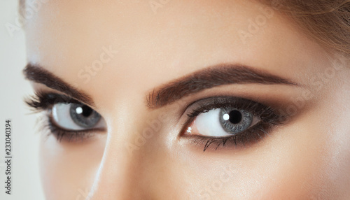 Beautiful Woman with long lashes and beautiful make-up looking at the camera.
