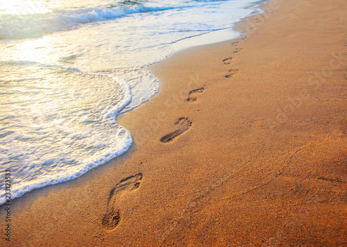 Fotografia beach, wave and footprints at sunset time