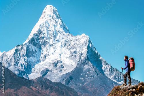 Carta da parati Hiker with backpacks reaches the summit of mountain peak