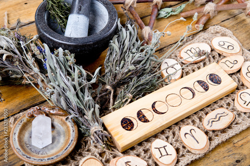 Foto Moon Phases and astrological symbols with herb witch mortar and pestle