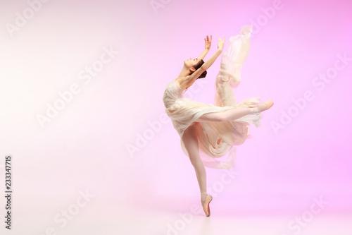 Valokuva Young graceful female ballet dancer or classic ballerina dancing at pink studio