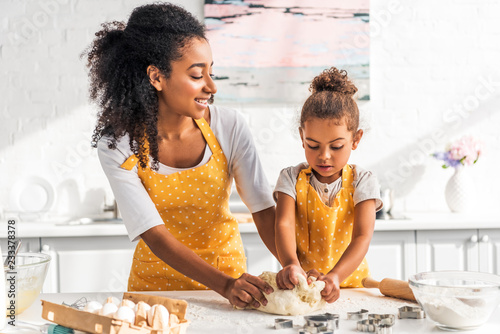 Fotografia attractive african american mother and adorable daughter kneading dough in kitch