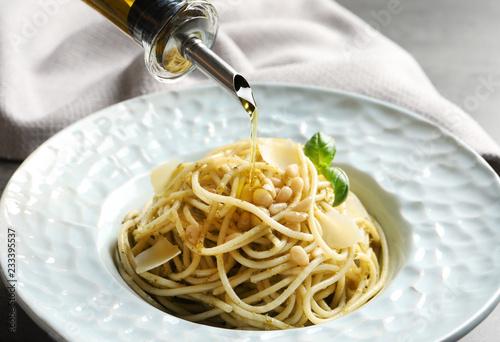 Dressing delicious basil pesto pasta with olive oil, closeup