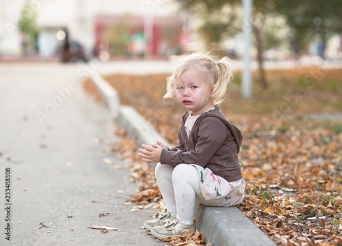Fényképezés Lost girl in the city. Sad baby girl sitting on the curb and cry