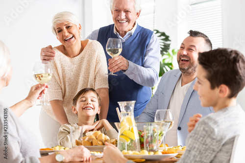 Smiling grandfather making toast during family dinner with happy boy and parents