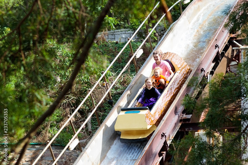 Carta da parati Family with kids on roller coaster in theme park.