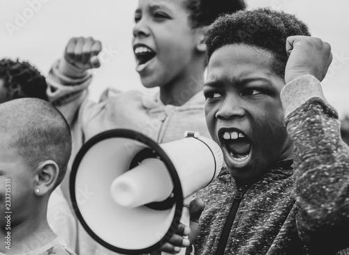 Obraz na plátně Young boy shouting on a megaphone in a protest