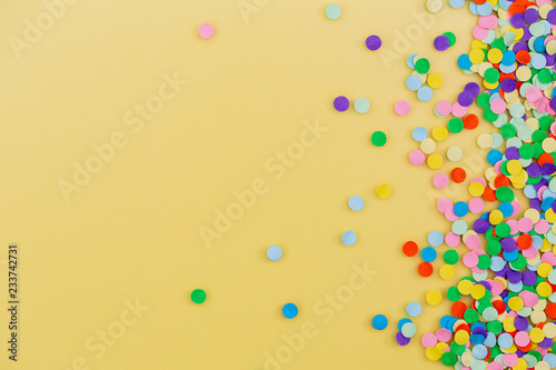 Colorful confetti on yellow background.