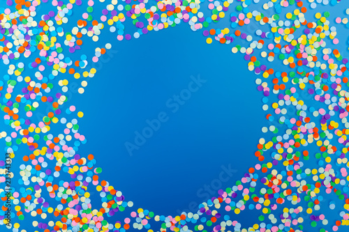 Round frame of colorful confetti on blue background.