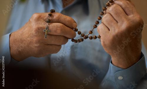 Obraz na plátně Praying hands of an old man holding rosary beads.