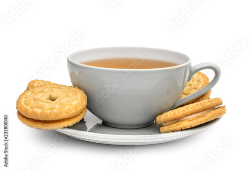 Stampa su Tela Cup of tea with sandwich cookies on on saucer. Isolated on white.