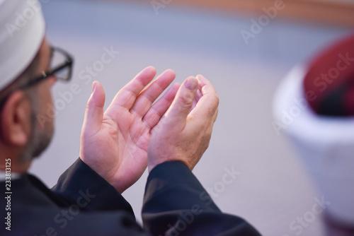 Elderly Muslim Arabic man praying during islamic conference