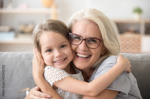 Happy old grandmother hugging little grandchild girl looking at camera, smiling mature mother or senior grandma granny laughing embracing adopted kid granddaughter sitting on couch, headshot portrait