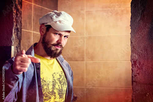Photo Brutal bearded man in a eight-blade cap indignantly frowned, pointing his finger