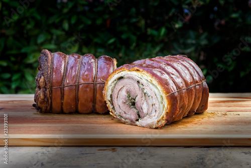 Roasted rolled pork cut in half on chopping board