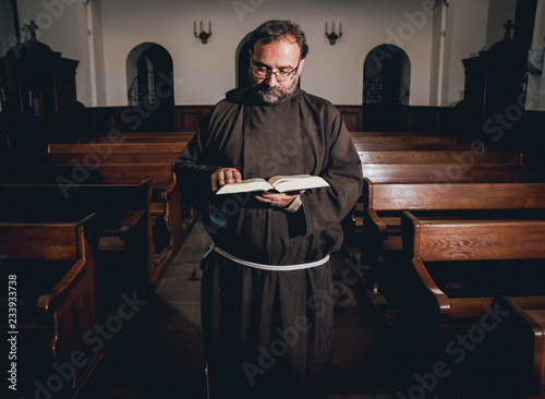 A monk in robes with holy bible in their hands praying in the church Fototapeta