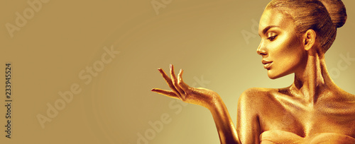 Golden woman. Beauty fashion model girl with golden skin, makeup, hair and jewellery on gold background. Fashion art portrait