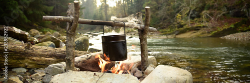 Fotografia Cooking food in pot over campfire outdoor