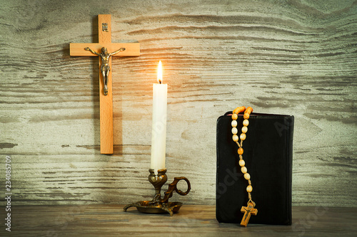 Fotografia Lighted candle, crucifix, and a book with a rosary