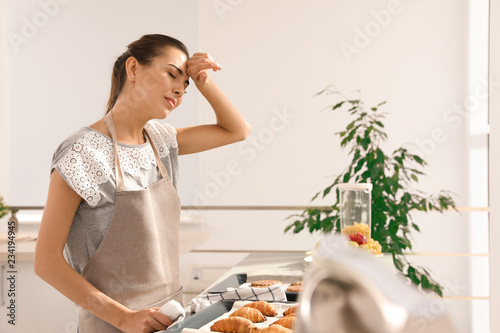 Tired woman with homemade oven baked pastry  in kitchen