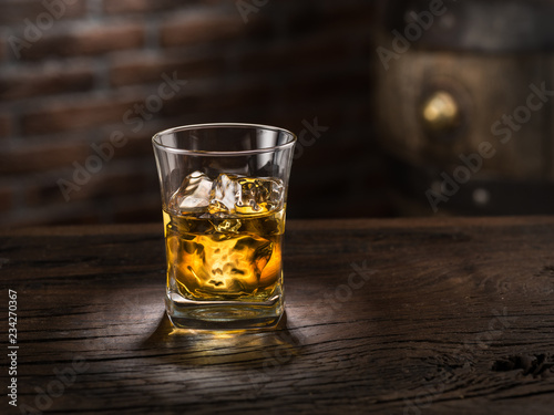 Obraz na plátně Whiskey glass or glass of whiskey with ice cubes on the wooden background