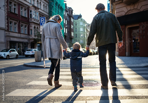 Foto A rear view of small toddler boy with parents crossing a road outdoors in city