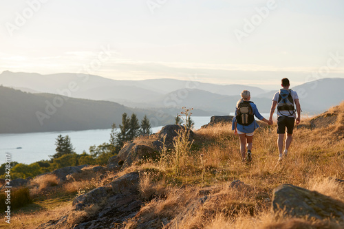 Obraz na plátně Rear View Of Couple Walking On Top Of Hill On Hike Through Countryside In Lake D