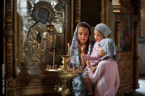 Fotografie, Obraz Young mother and her little blond Caucasian daughter with candles in Orthodox Ru