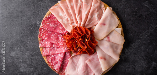 Cold meat on cutting board on black stone Top view,panoramic view. Ham, salami, sausage mortadella and turkey