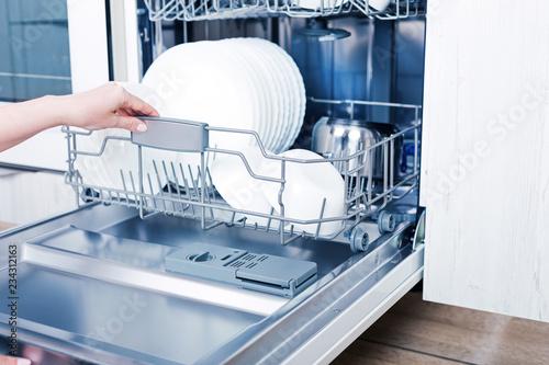 Home appliance dishwashing machine in kitchen interior, no people
