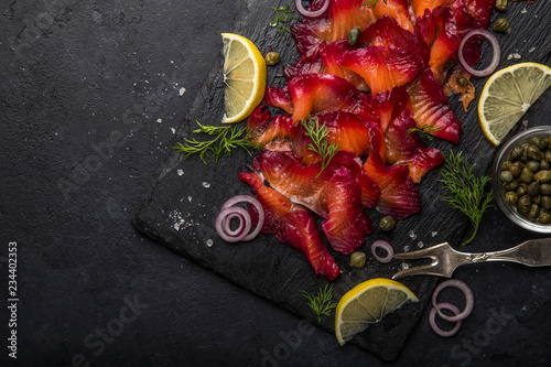 Fotografia sliced Gravlax,  scandinavian beet cured salmon  served with red onion, capers a