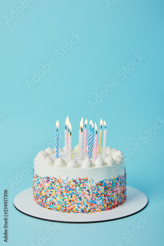 Tasty birthday cake with lighting candles on blue background Fototapete