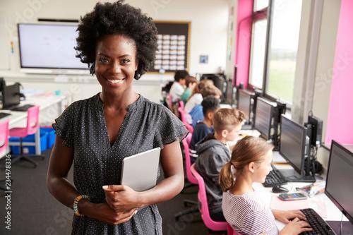 Fotografie, Obraz Portrait Of Female Teacher Holding Digital Tablet Teaching Line Of High School S